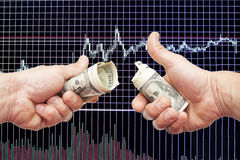 Dollar notes in hands on a black background with the schedule. Of Japanese candles and indicators stock image