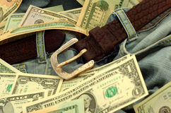 Dollar notes and old jeans. A lot of dollar notes with old blue jeans together royalty free stock image