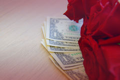 Dollar notes with red roses on the table Royalty Free Stock Images