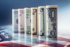 Dollar och amerikanska flaggan Amerikanska dollarsedlar rullade i olika positioner och USA flaggan i bakgrunden Royaltyfria Foton