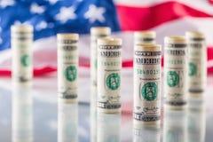 Dollar och amerikanska flaggan Amerikanska dollarsedlar rullade i olika positioner och USA flaggan i bakgrunden Royaltyfria Bilder