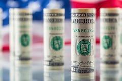 Dollar och amerikanska flaggan Amerikanska dollarsedlar rullade i olika positioner och USA flaggan i bakgrunden Arkivfoto
