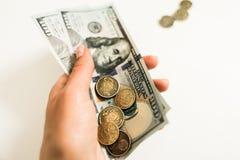 Dollar och cent p? vit bakgrund arkivfoto