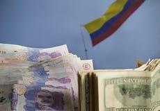 Dollar och colombianska pengar med den colombianska flaggan som vinkar i bakgrunden arkivfoto