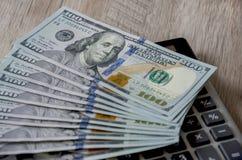 Dollar och en räknemaskin på en grå träbakgrund royaltyfria bilder