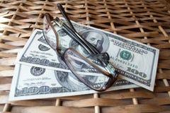 Dollar och exponeringsglas Arkivfoto