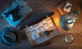 Dollar packs and gun. Vintage desktop in the dark with a gun, a briefcase and a lot of dollar packs, top view Royalty Free Stock Images