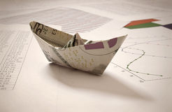 Dollar paper boat on financial data Stock Photography