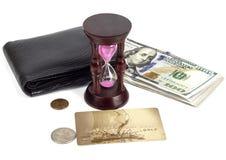 Dollar plast- kort, handväska, timglas på en vit bakgrund royaltyfri foto