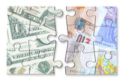 Dollar pound currency jigsaw. Jigsaw puzzle consisting of dollar and british pound money banknotes over a white background Stock Photo