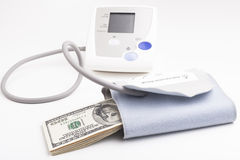 Dollar Pressure. Electronic blood pressure meter with dollar banknotes  on white background Royalty Free Stock Photography