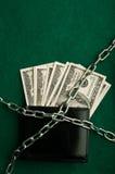 Dollar räkningar och metallkedja Arkivbild