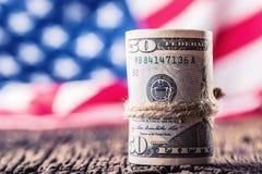 Dollar rollten Banknotennahaufnahme mit amerikanischer Flagge im Hintergrund Bargeld-Amerikaner-Dollar Großaufnahme des Stapels U Stockfotos