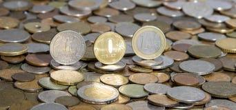 Dollar, rouble et euro sur le fond de beaucoup de vieilles pièces de monnaie Photographie stock libre de droits
