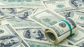 Dollar roulé cent sur le billet d'un dollar américain d'argent de fond Beaucoup billet de banque des USA de 100 Photographie stock