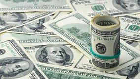 Dollar roulé cent sur le billet d'un dollar américain d'argent de fond Beaucoup billet de banque des USA de 100 Photos stock