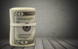 Dollar rullar draget åt med musikbandet på trätabellen Royaltyfri Fotografi