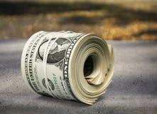 Dollar rullar draget åt med musikbandet på trätabellen Arkivbilder