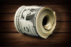 Dollar rullar draget åt med musikbandet på trätabellen Royaltyfri Foto