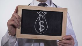 Dollar sack drawn on blackboard in doctor hands, expensive medicine, bribery. Stock footage stock video footage