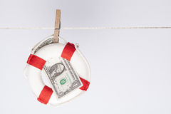 Dollar saver. Clothespin fixing a safety buoy with a one dollar banknote on a clothes line. financial concept for currency risk or protection Royalty Free Stock Image