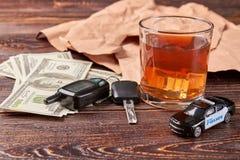 Dollar, Schlüssel, Whisky, Polizeiwagen Stockfotografie