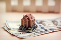 Dollar sedlar som hus och räknemaskinen på en vit bakgrund Dollarsedel med huset Arkivfoto