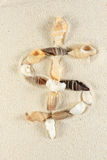 Dollar sign. Made of seashells group on the sand stock photography