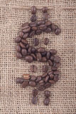 Dollar sign of coffee beans on jute. Dollar sign of dark roasted coffee beans on jute Royalty Free Stock Photography