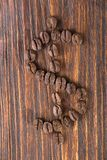 Dollar sign from coffee seeds on a wooden background. Close up Stock Photos