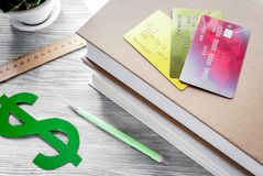 Dollar sign and credit cards for fee-paying education on gray st. Dollar sign and credit cards for fee-paying education on gray wooden student desk background stock image