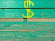 Dollar sign drawn in yellow paint on a green wooden bench. Dollar sign drawn yellow paint green wooden bench concept emblem strong drawing payment plan money stock photo