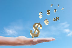 Dollar Sign on hand. On blue sky background Royalty Free Stock Photography