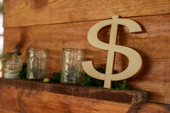 Dollar sign. The dollar sign out of wood standing on a wooden shelf decor zone royalty free stock photos