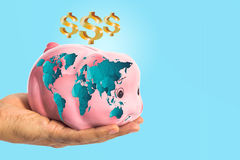 Dollar sign over piggy bank with worldmap in male hand Royalty Free Stock Photos
