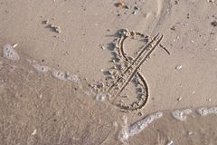 Dollar sign painted on the sand of beach is washed off by a sea. Wave. Close up shot Stock Photography
