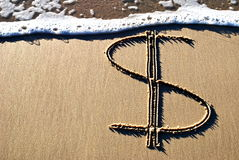 Dollar sign on sand. Dollar sign written in the sand with wave about to wash over it stock image