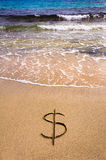 Dollar sign  in the sand being washed away. Currency concept Royalty Free Stock Photos