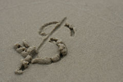 Dollar sign on the sand. Dollar sign written in wet sand royalty free stock images