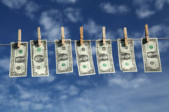 Dollar sky. Dollar bills hanging on a line with a blue sky as backdrop Stock Photography