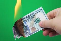 100 dollar som bränner på en grön bakgrund Begrepp av nedgång i ekonomi och förlust royaltyfri foto