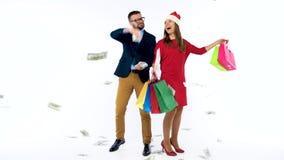 Dollar som faller på formellt klädd man och kvinna i den Santa Claus hatten Låt ` s gå ferieshopping och fira lager videofilmer