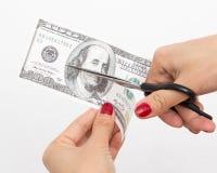 100 dollar som klipps med sax på vit Fotografering för Bildbyråer