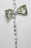 Dollar Squeeze High Hang. Dollar bill being squeezed by tape measure on white background stock image