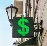 Dollar symbol on a diode panel. On a building wall stock photography