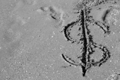 Dollar symbol drawn on the sand. On beach,sunny weather day, monochrome stylized stock photography