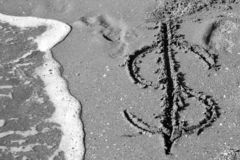 Dollar symbol drawn on the sand. On beach,sunny weather day, monochrome stylized royalty free stock photography