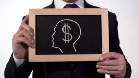 Dollar symbol head image on blackboard in businessman hands, greed for money. Stock footage stock photo
