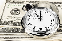 Dollar Timing. Silver stopwatch closeup 5 sec on a pile of hundred dollar bills royalty free stock photography