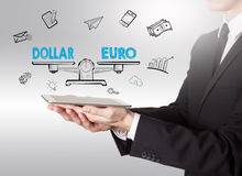Dollar und Euro balancieren, der junge Mann, der einen Tablet-Computer hält Stockfotos